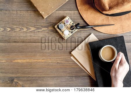 author office in professional writer concept with hands, hat and cup on wooden work desk background top view mock up