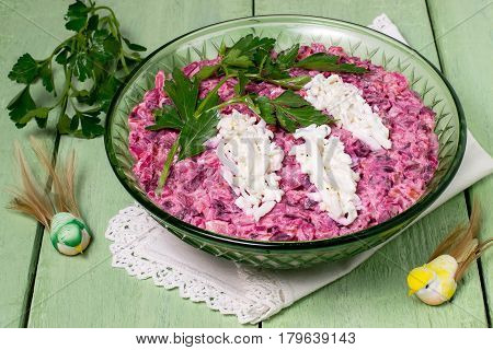 Festive salad with beets smoked fish and eggs on green wooden table. Original decoration of egg and parsley in the form of flowering twig of bird cherry. The idea of festive recipe for Mother's Day