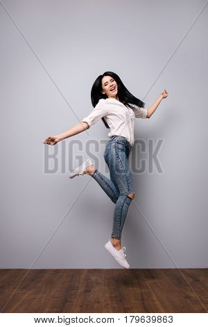 Full Portrait Of Happy Laughing Jumping Woman Who Is Excited Because Of Passing All Exams At Univers