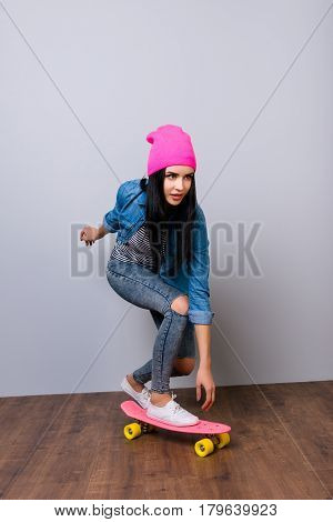 Vertical Portrait Of Young Pretty Woman In Jeans And Pink Hat Skateboarding Against Gray Background
