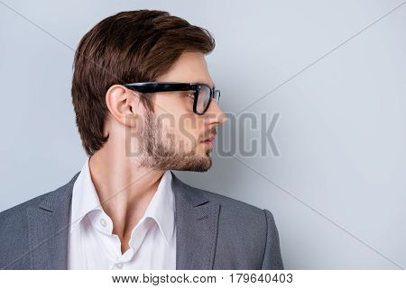 Side-view Portrait Of  Young Successful Serious Man With Bristle In Glasses And Wearing  Suit  Stand