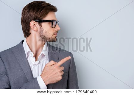 Side View Portrait Of Young Businessman In Glasses And Formalwear Pointing On Copyspace