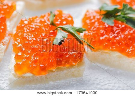 Sandwiches with salmon red caviar and herbs on white napkin. Close up image with selective focus.