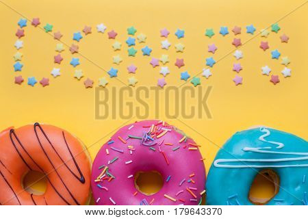 A Set Of Sweet Donuts On Orange Background. Above The Inscription Donuts From Sugar Stars