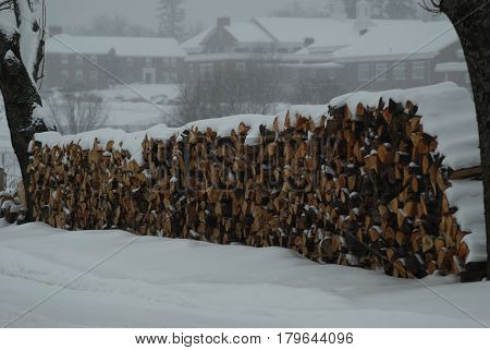 Large wood pile during snow storm waiting to be burned in front of New England prep school