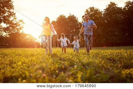 Young cheerful family together enjoying outside
