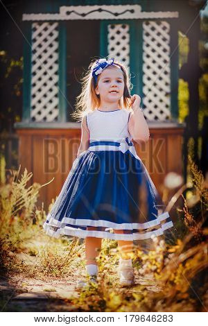 Girl in a blue dress on a background of old wells. The child is on the trail, along with dry grass. The little girl straightens hair.