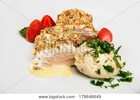Meat covered in crumpet of pumpkin seeds served on plate.. Close-up, white background.