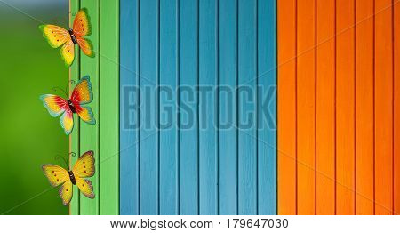 Metal outdoor butterflies wall art over colorful fence