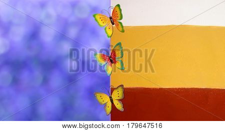 Colorful butterflies over blurred purple background and colorful fence