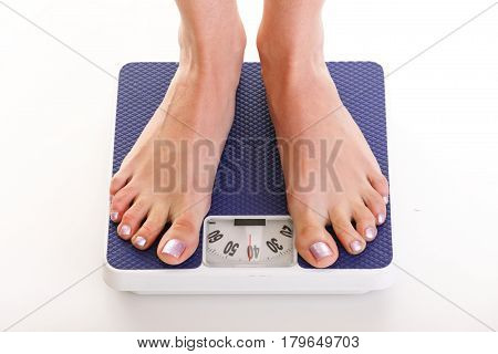 Woman Feet And Weight Scale Isolated On White Background