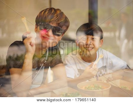 Asian mother & son smiling at camera when eating