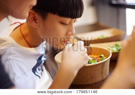 Asian mother & son have lunch in a restaurant