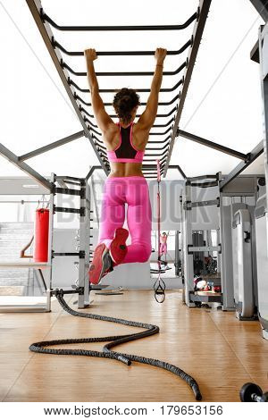 Brunette fitness woman in pink sport wear with perfect fitness body training on horizontal bar in gym