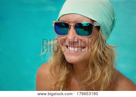 Trendy Beautiful Young Woman in hat and sunglasses posing  turquoise Background