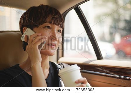 Asian woman making a phone call in cab