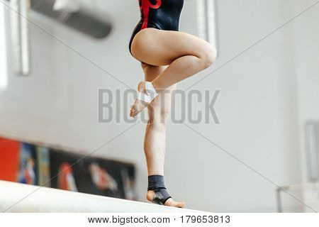 competition in artistic gymnastics female gymnast exercises on balance beam