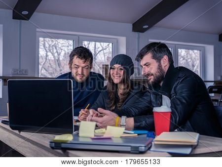 Video conference of young smart team. Group of modern people discussing project on video conference in the office. Working environment with laptop coffee notepads and stationery. Business team concept