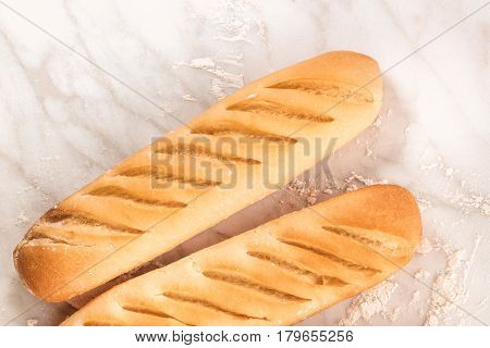 An overhead photo of freshly baked loaves of white bread on a white marble texture with flour and a place for text