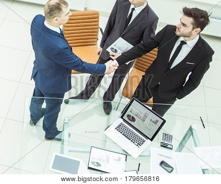 assistant with financial documents and business partners shake hands before starting a business meeting