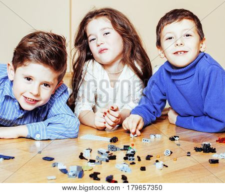 funny cute children playing toys at home, boys and girl smiling, first education role lifestyle close up