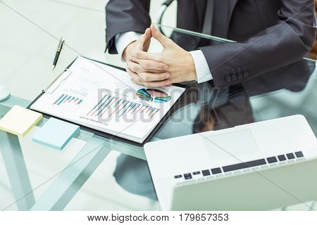 closeup of a businessman ponders the financial policy of the company sitting behind a Desk in the office