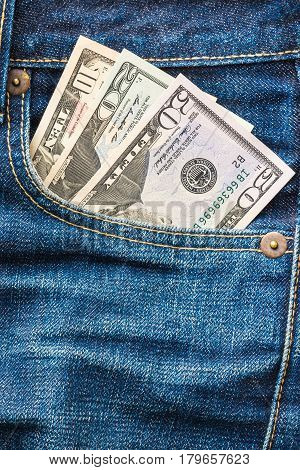 American money (US currency, USD) in the back pocket of indigo blue jeans
