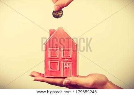 Man Putting Coin Into House Piggybank