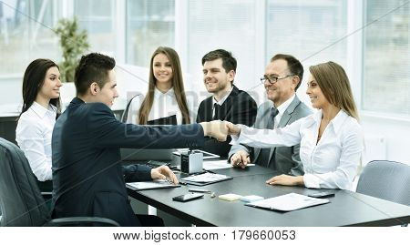 handshake business partners at a meeting in creative office on the background