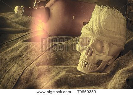 The human skull lying on a tarpaulin against the background of a bottle with a flare from the fire in the foreground brings fear and death