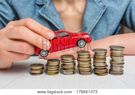 Businesswoman And Toy Car On Coin Stack