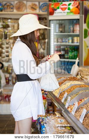 CYPRUS, TROODOS - 06 MAY 2012: Smiling woman in a store is buying products