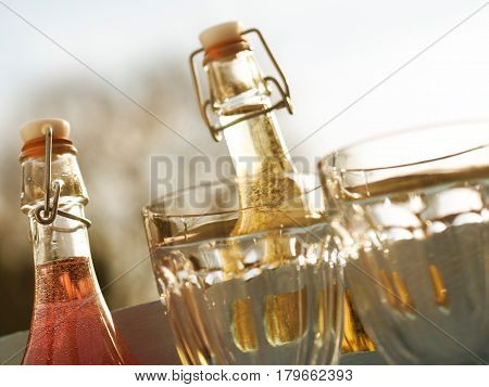 Summer drinks in a rustic wooden box with glasses in a garden at sundown