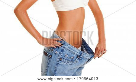 Woman shows her weight loss by wearing an old jeans, isolated on white background. Close up of sporty and beautiful female body.  Healthy lifestyle, dieting, fitness, weight loss concept