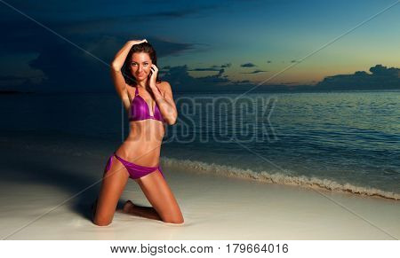 Woman in bikini on the beach sunset background. Happy lifestyle. White sand, sunset sky and crystal sea of tropical beach. Sexy tanned woman on the summer beach.
