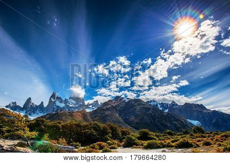 Mount Fitz Roy in Patagonia in Argentina and its neighboring granite towers with lens flare from the sun as seen from hike towards Laguna de los Tres