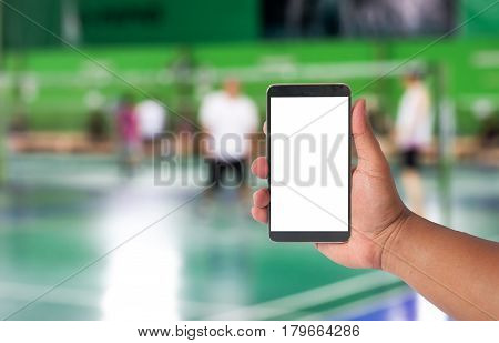 Hand Hold Mobile Phone Over Blurred Of Badminton Court With Players Playing Badminton.