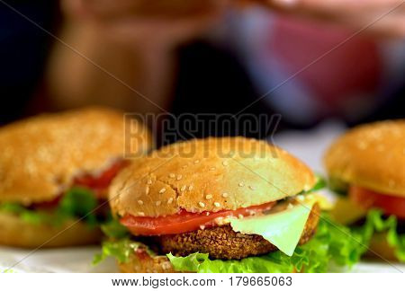 Hamburger fast food with ham on wooden board . Group of hamburger. Piece of cheese hanging from sandwich on blurry field.