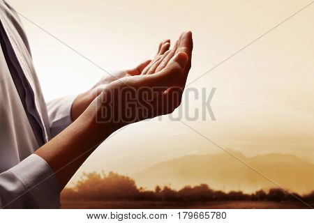 Muslim man prayingt o god at sunset