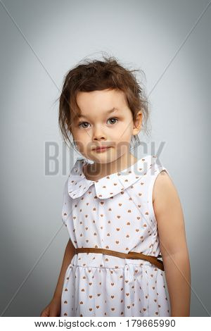 Portrait of 3 year old little girl with dress, surprised looks on bright white background
