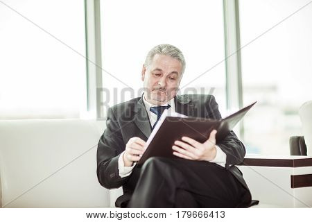 experienced lawyer reviews the documents with the terms of a new contract sitting on the sofa in the private office.