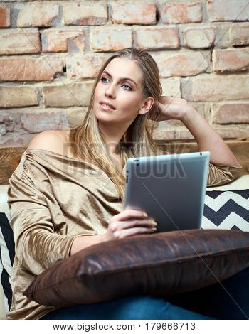 Daydreaming young woman resting on sofa at home, using tablet computer.