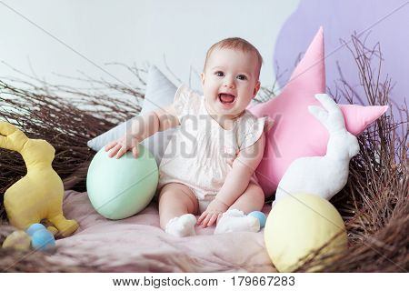 Happy baby girl in big Easter nest with eggs. Easter holiday concept: nest with baby hare.