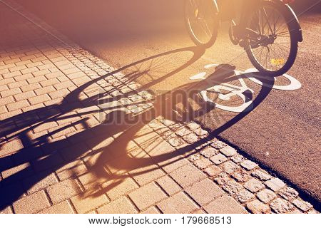 Shadow of unrecognizable cyclist riding a bike on bicycle lane through city street next to the road marking in urban surrounding retro toned