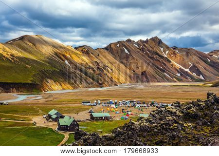 Iceland in July. Great Valley Park Landmannalaugar, surrounded by mountains of rhyolite and unmelted snow. In the valley built large camp. The concept of world tours. Trend