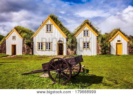Houses and ancient rural two-wheeled wheelbarrow. The concept of the historical and cultural tourism. Interesting ethnographic museum Glaumbaer in Iceland