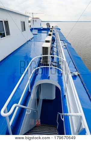 Ladder leading to captain's cabin of cruise river motor ship. Ship is moving along Uglich reservoir