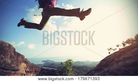 jumping over precipice between two rocky mountains . freedom risk challenge success concept