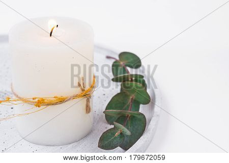 White candle on grey tray eucalyptus branch styled stock image for product and social media marketing copyspace