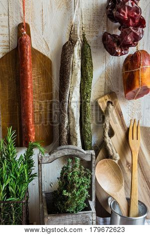 Variety of Spanish cured meat products charcuterie fresh rosemary wood cutting board kitchen utensils hanging on hooks